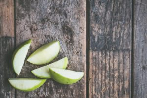 Green Apple Slices Sitting on Wooden Table | BlairCandy.com